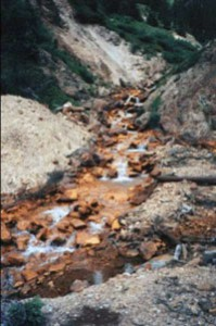 When pyrite mixes with air and water to produce sulfuric acid, iron is left to settle out giving areas where this happens an orange rust color – a tell-tale sign of acid mine drainage.