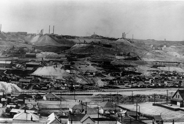 The Butte Hill in the 1890's. Notice the thick smog in the sky, produced by the numerous small smelters in the city at the time. Also note the expansive piles of acidic waste rock.